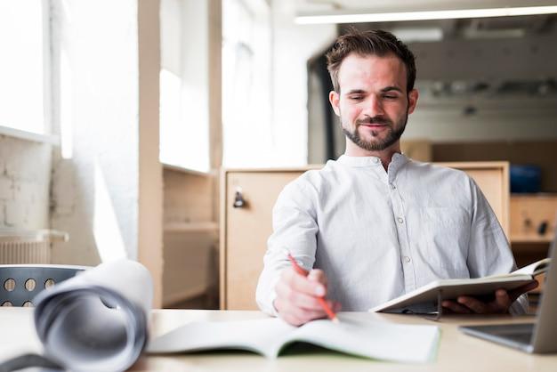 オフィスで働く椅子に座っている若い男の笑みを浮かべてください。 無料写真