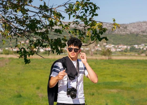緑の風景の上に立ってカメラを持つ若い写真家 無料写真