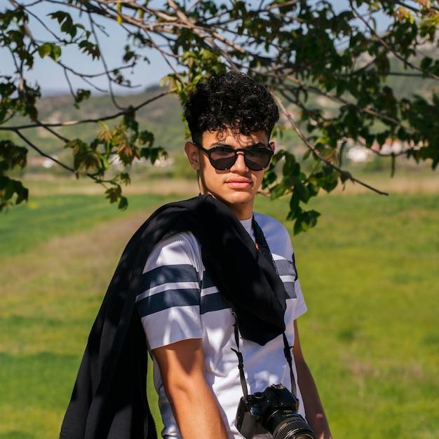 サングラスとデジタルカメラを着てカメラを見て魅力的な若者の肖像 無料写真