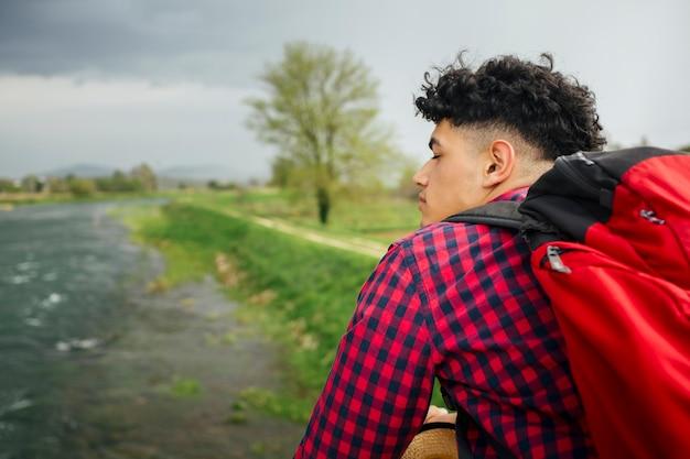 川の近くに立っているバックパックを運ぶ男 無料写真