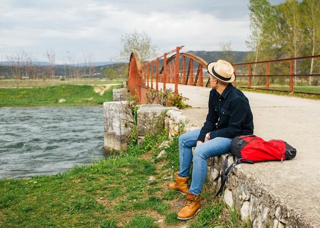 男は流れる川の土手銀行をリラックスします。 無料写真
