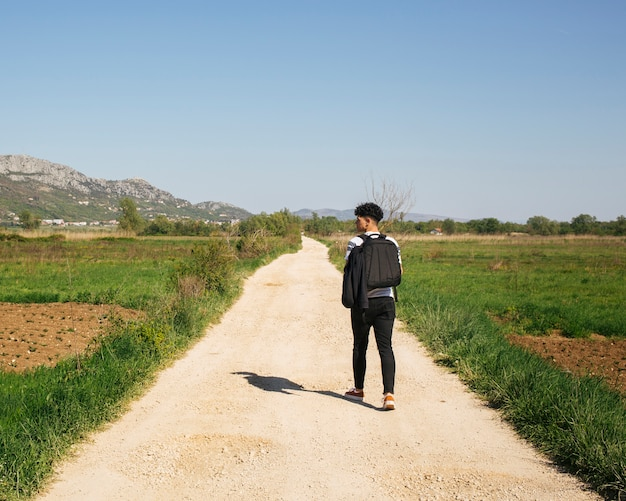 Вид сзади молодого мужского путешественника, идущего в сельской местности, несущей рюкзак Бесплатные Фотографии