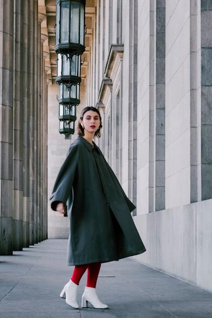 Модная молодая женщина, стоящая под строкой освещенного оборудования Бесплатные Фотографии