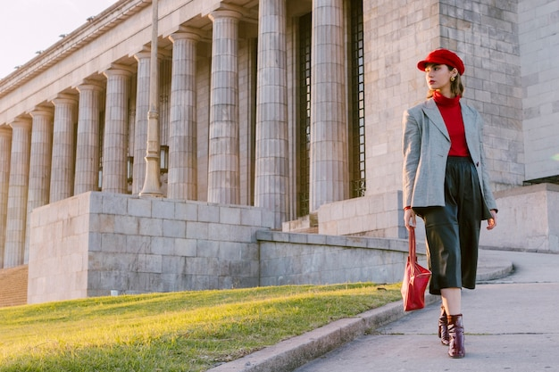 赤い帽子と離れているハンドバッグを着ている美しい若い女性 無料写真