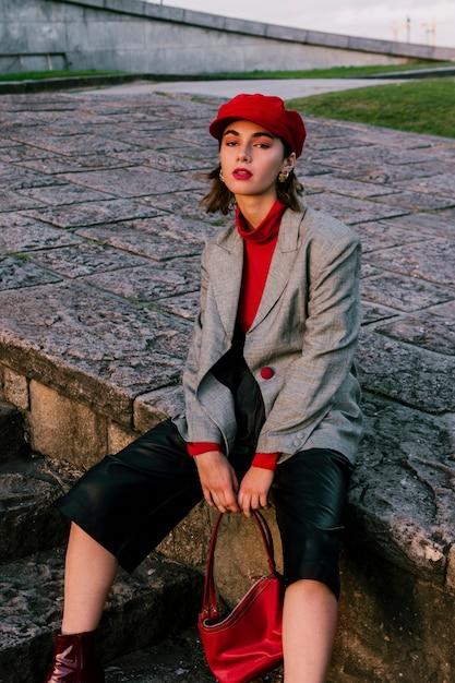 Привлекательная стильная молодая женщина держит сумочку в руке Бесплатные Фотографии