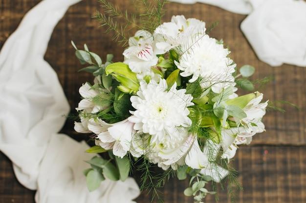 木製のテーブルの上のスカーフと装飾的な白い花の花束 無料写真