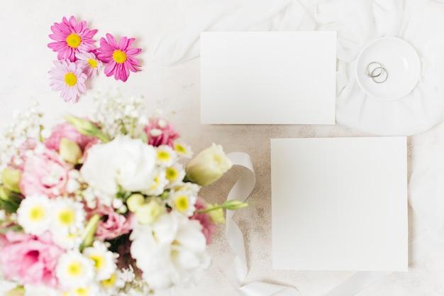 白いカードとコンクリートの背景にリングのウェディングブーケの俯瞰 無料写真