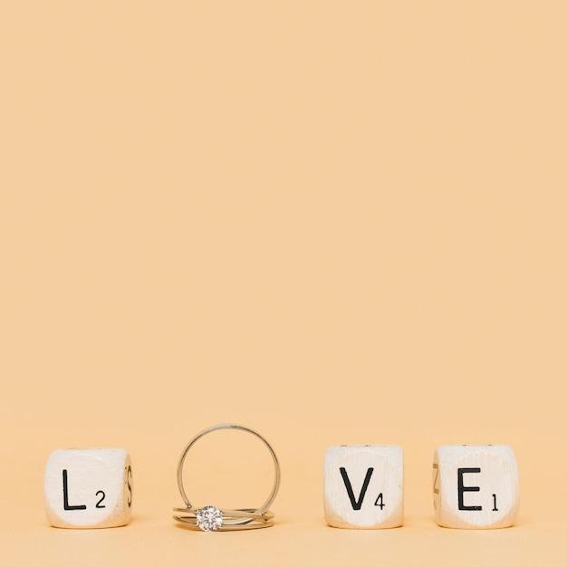 結婚式のダイヤモンドの指輪とクリーム色の背景上のキューブで作られたラブレター 無料写真