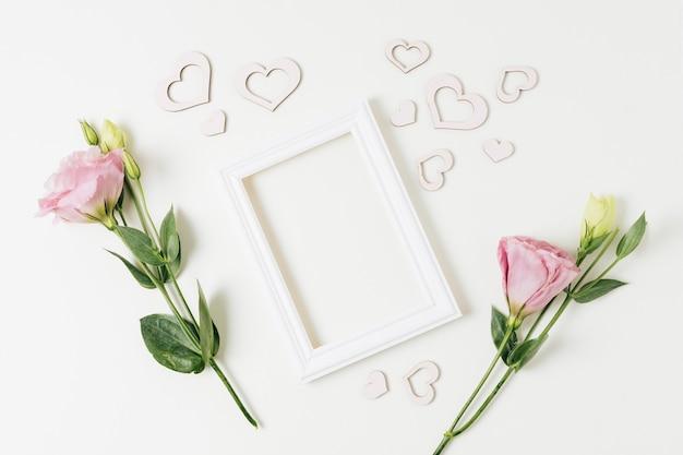 Белая рамка с сердечками и цветами эустомы на белом фоне Бесплатные Фотографии