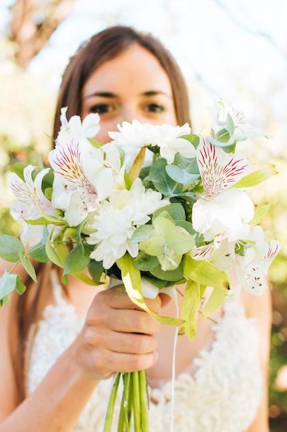 Крупный план невесты, держащей букет белых цветов перед ее лицом Бесплатные Фотографии