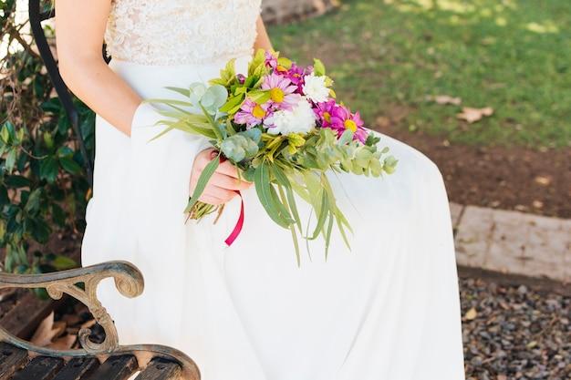 花の花束を手に保持している白いウェディングドレスの花嫁 無料写真