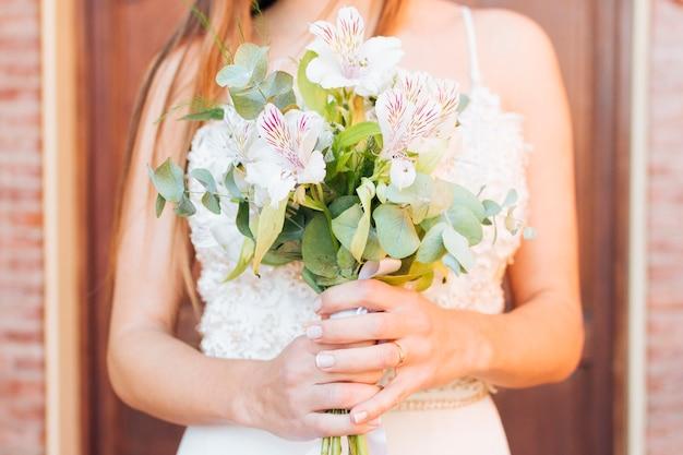 美しい花の花束を保持している花嫁の手の半ばセクション 無料写真