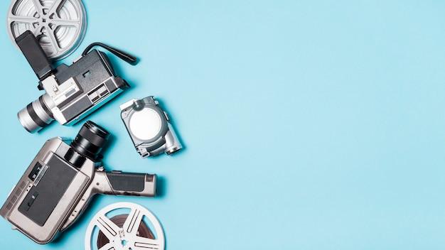 フィルムリールと青色の背景にさまざまな種類のビデオカメラ 無料写真