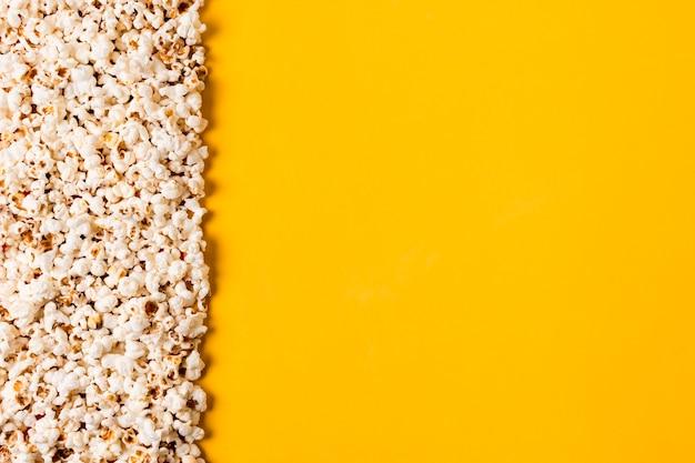 黄色の背景に広がるポップコーン 無料写真