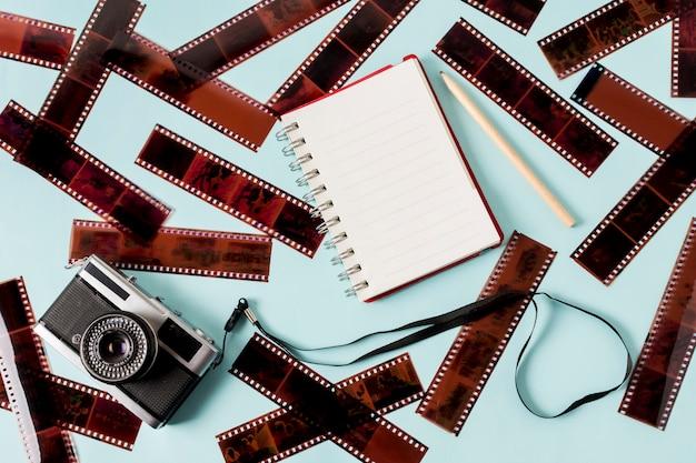 Пустой спиральный блокнот; карандаш и камера с негативными полосами на синем фоне Бесплатные Фотографии
