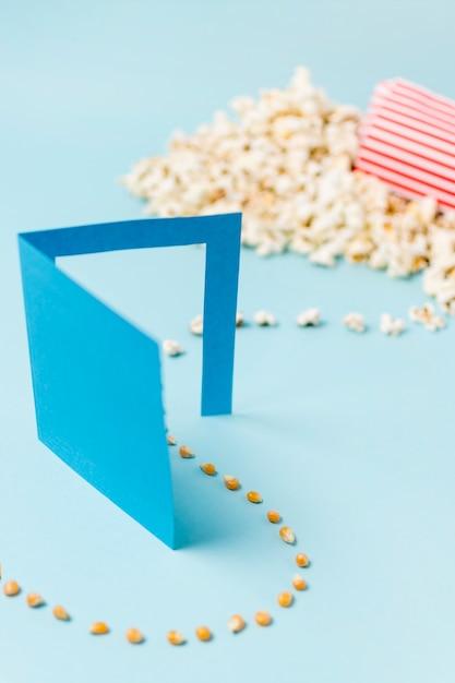 ポップコーンの種は青い背景にポップコーンに変身紙のドアを通って入る 無料写真