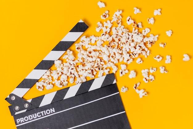 黄色の背景にポップコーンと映画カチンコ 無料写真
