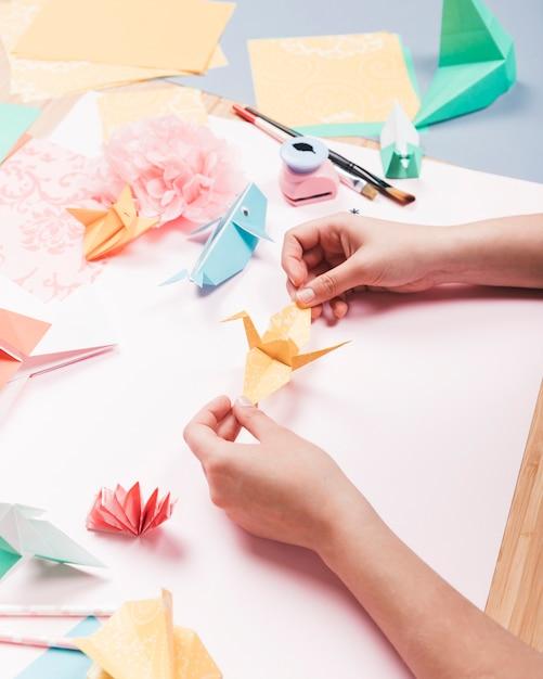 Вид сверху человеческой руки, держащей оригами птица над столом Бесплатные Фотографии