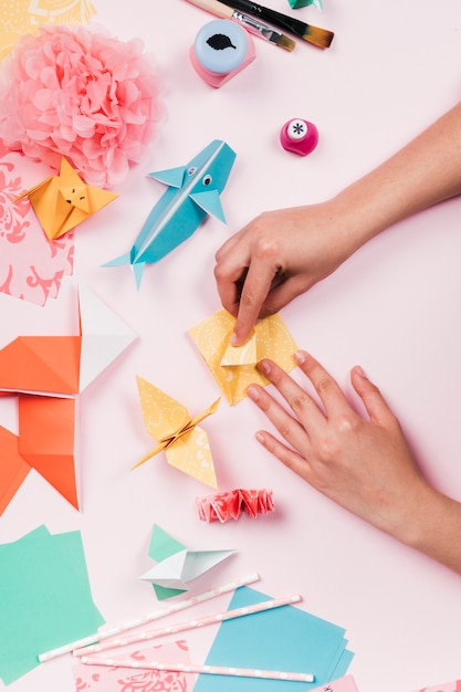 Повышенный вид мастерицы, делающей ремесло из бумаги оригами Бесплатные Фотографии