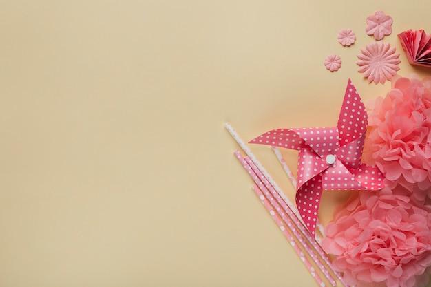 クリエイティブ風車。紙の花とベージュの表面上のわら 無料写真