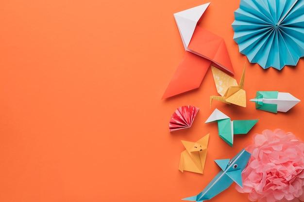 明るいオレンジ色の表面に折り紙の紙工芸品のセット 無料写真