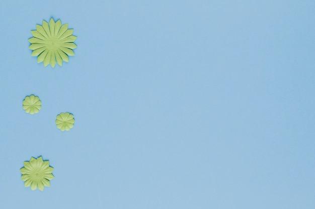 青色の背景に装飾的な緑の花の切り欠きの高角度のビュー 無料写真