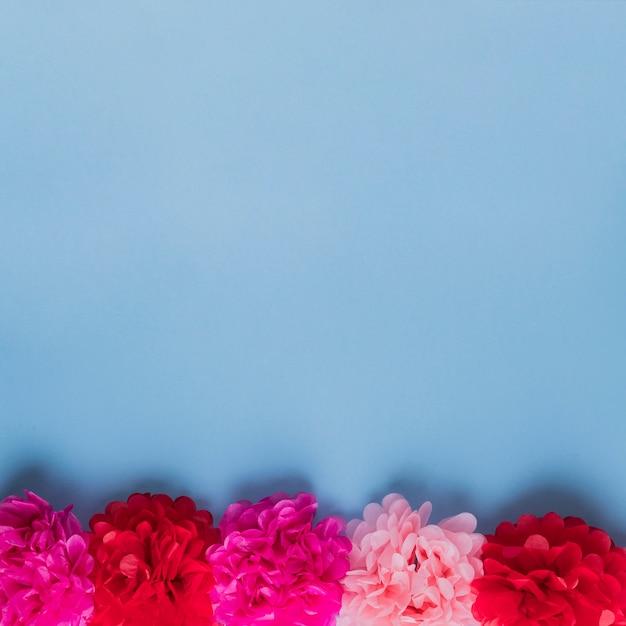 青い表面上に配置された赤とピンクの紙の花の行 無料写真
