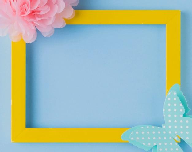 花と蝶の切り欠きを持つ装飾的な黄色のフォトフレームのオーバーヘッドビュー 無料写真