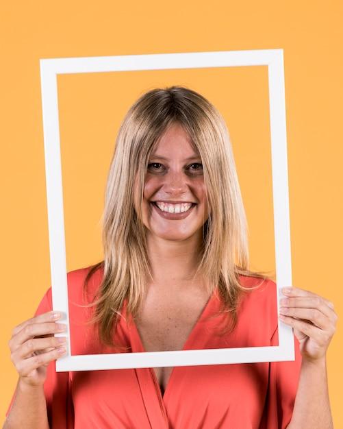 彼女の顔の前で白い枠フォトフレームを保持している若い笑顔の女性 無料写真
