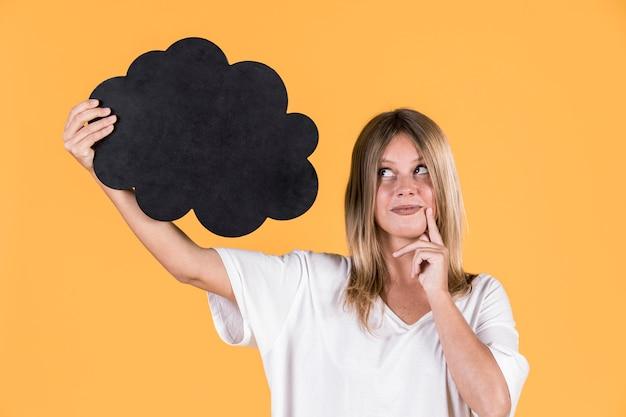Крупный план женщины, держащей пустой речи пузырь над желтой поверхностью Бесплатные Фотографии