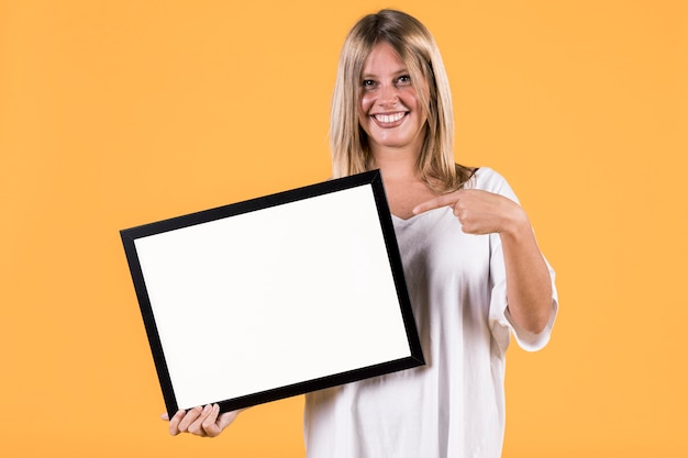 空の白い額縁で若いブロンドの女性人差し指を無効にします。 無料写真