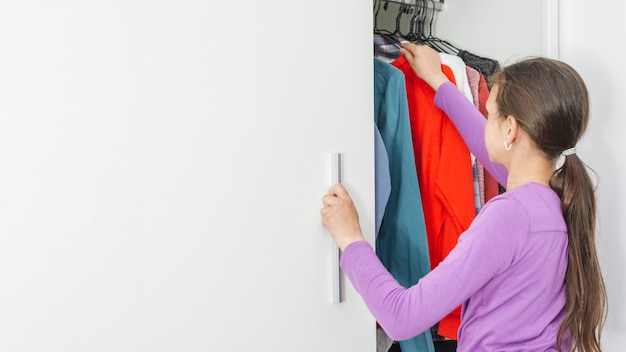 女の子は学校のための服を選ぶ 無料写真