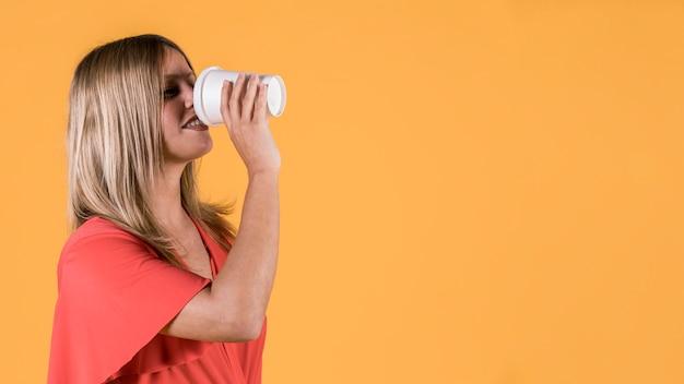 黄色の背景上の使い捨てのガラスにジュースを飲む若い女性の笑みを浮かべてください。 無料写真