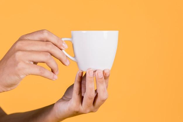 黄色の背景に対してティーカップを持っている人の手のクローズアップ 無料写真
