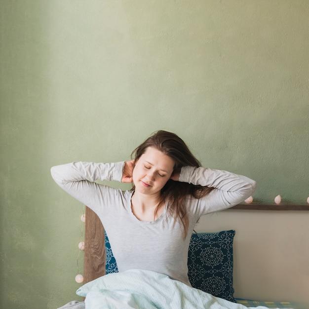 彼女のベッドでリラックスした女性 無料写真