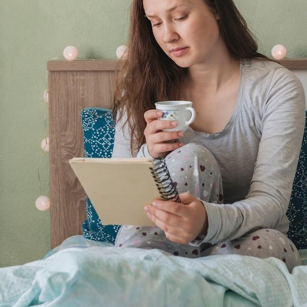 女性がベッドにいる間読書 無料写真
