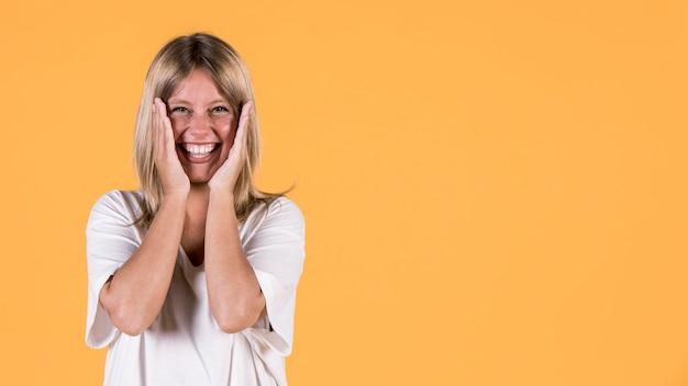 黄色の背景の上にカメラを見て驚いた聴覚障害者の女性の肖像画 無料写真