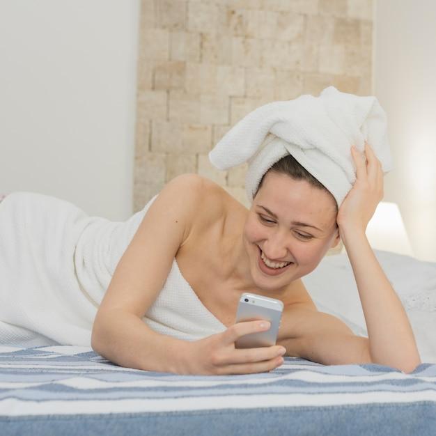 シャワーの後ベッドでスマートフォンを見ている女性 無料写真