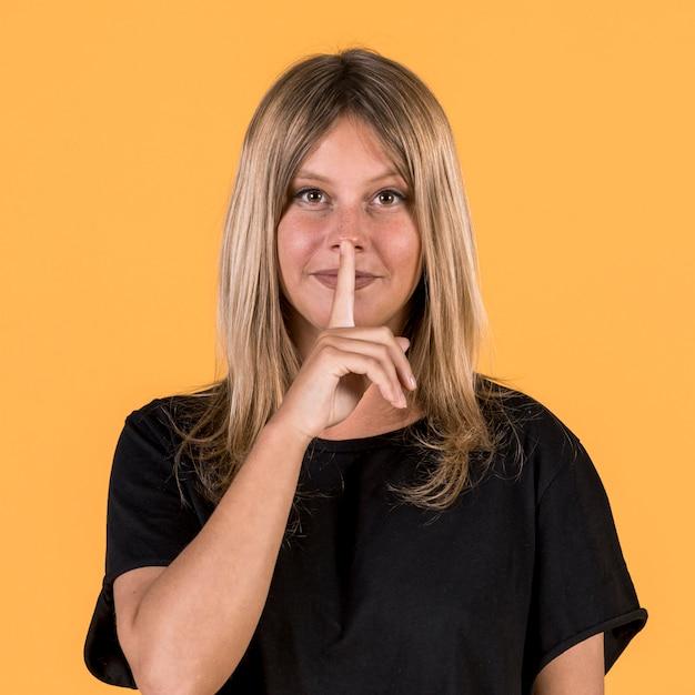 黄色の背景の前で静かなジェスチャーで聴覚障害者の女性の正面図 無料写真