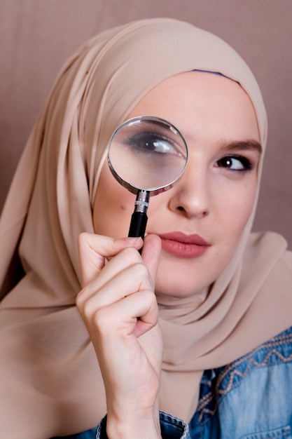 虫眼鏡を通して見る好奇心が強いイスラム教徒の女性のクローズアップ 無料写真