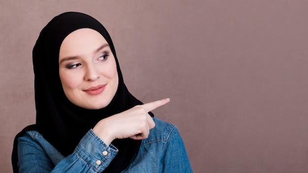 背景を指して笑顔のきれいな女性 無料写真