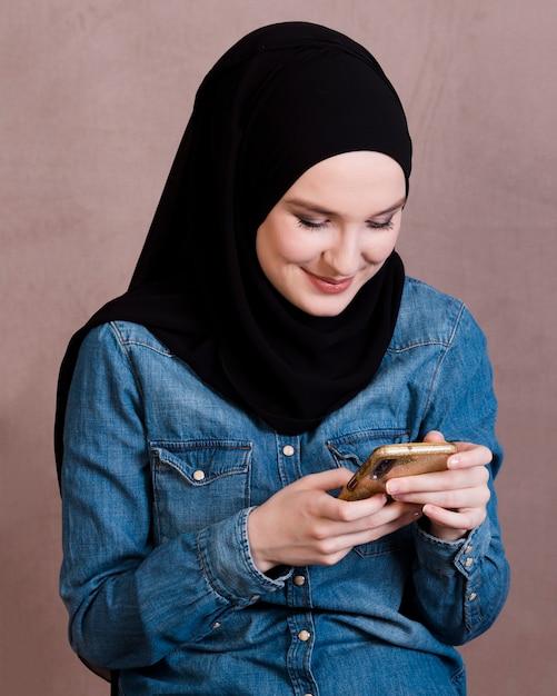 魅力的な笑顔の女性を背景に携帯電話を使用して 無料写真