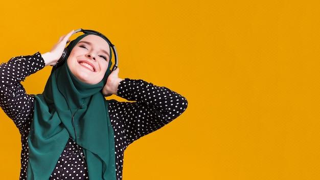 幸せなイスラム教徒の女性が黄色の表面に対してヘッドフォンで曲を聴く 無料写真