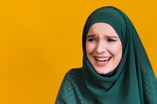 黄色の背景に対してよそ見うれしそうなイスラム女性 無料写真