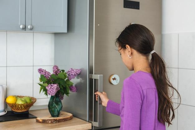 Девушка открывает холодильник на кухне Бесплатные Фотографии