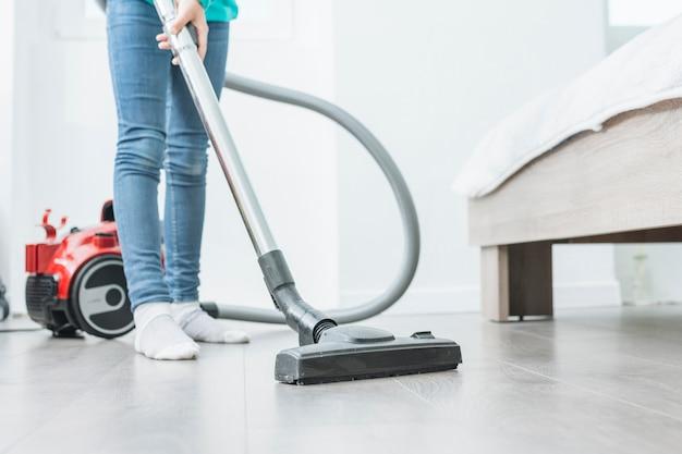 女性が自宅で掃除機を使用して 無料写真