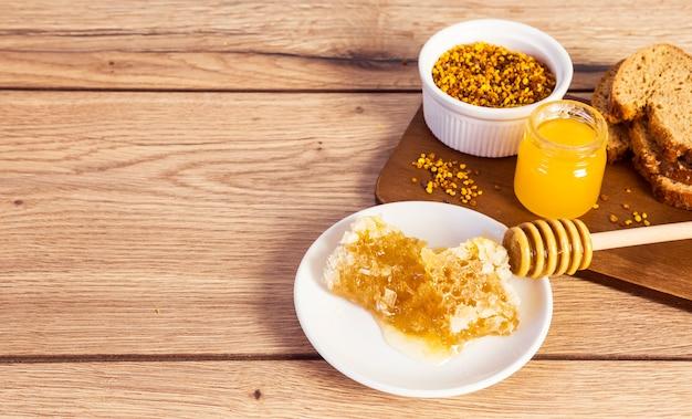木製のテーブルに蜂蜜と蜂蜜のアクセサリーとパンのスライス 無料写真