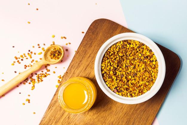 蜂の花粉と白い背景の上の木製のまな板の上に蜂蜜の瓶 無料写真
