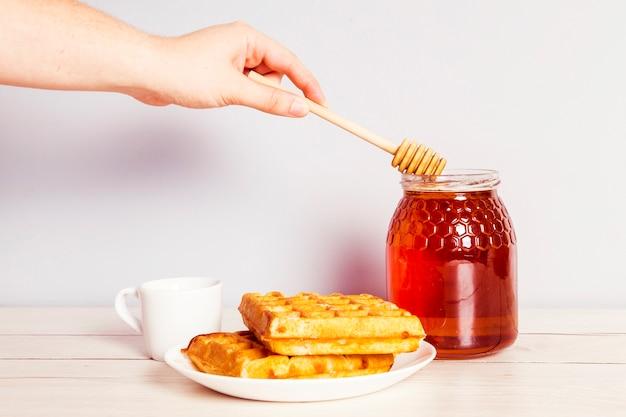 朝食に瓶から蜂蜜を選ぶひしゃくを持つ人の手 無料写真