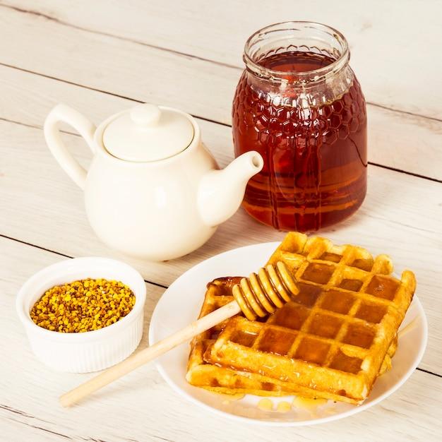 Запеченная вафля; мед; чайник и пчелиная пыльца на деревянный стол Бесплатные Фотографии